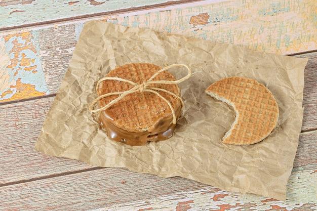 Gros plan d'une pile de stroopwafels sur un papier brun, à côté d'un autre biscuit avec une bouchée (vue de dessus).