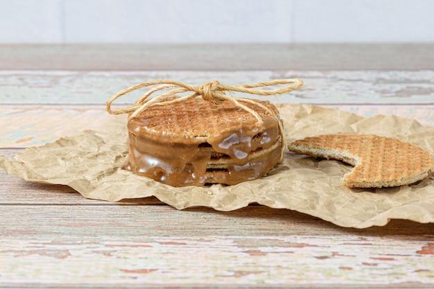 Gros plan d'une pile de stroopwafels sur un papier brun, à côté d'un autre biscuit avec une morsure (vue latérale).