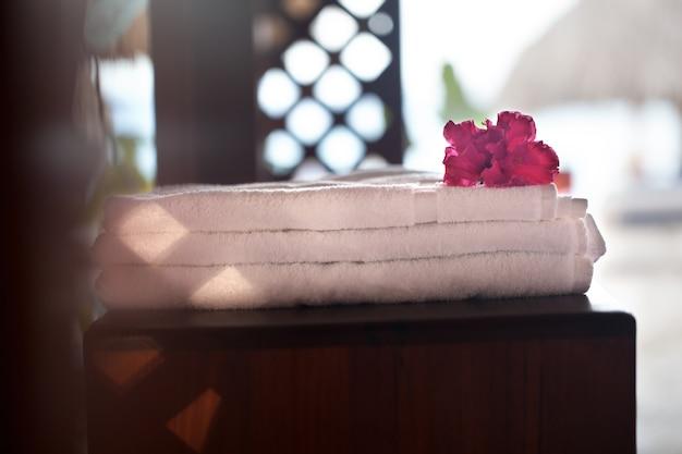 Gros plan d'une pile de trois serviettes blanches fraîches avec une fleur rose sur le dessus.