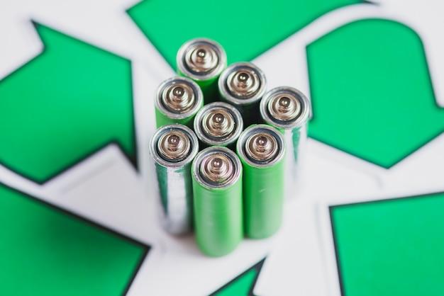 Gros plan de piles vertes avec l'icône de recyclage sur fond blanc