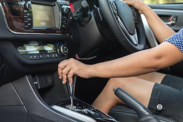 Gros plan pilote gauche main déplaçant le levier de vitesse dans la voiture
