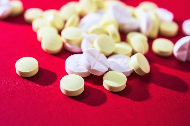 Gros plan de pilules blanches et jaunes sur fond rouge