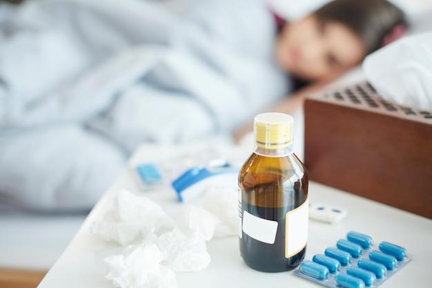 Gros plan sur des pilules et du sirop avec une femme au lit