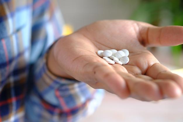 Gros plan de pilules médicales blanches sur la paume de la main