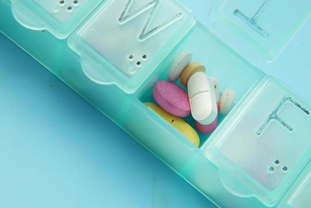 Gros plan de pilules médicales dans une boîte à pilules sur fond de couleur