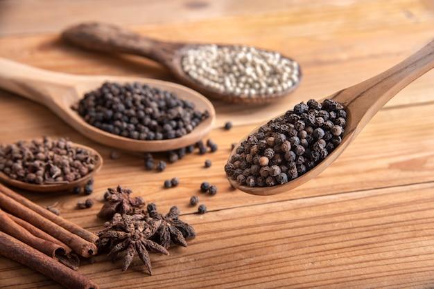 Gros plan, piment, poivre, cuillère, bois, entourer, à, poudre épice, sur, table bois