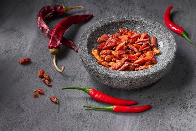 Gros plan sur les piments chili frais sur une table texturée sombre et les secs dans un bol en pierre