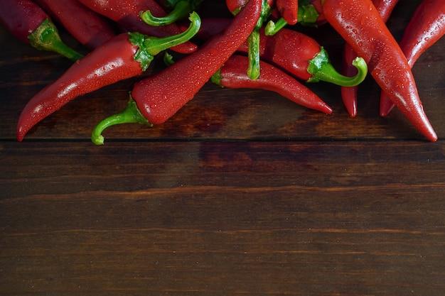 Gros plan des piments rouges frais et humides sur une table en bois