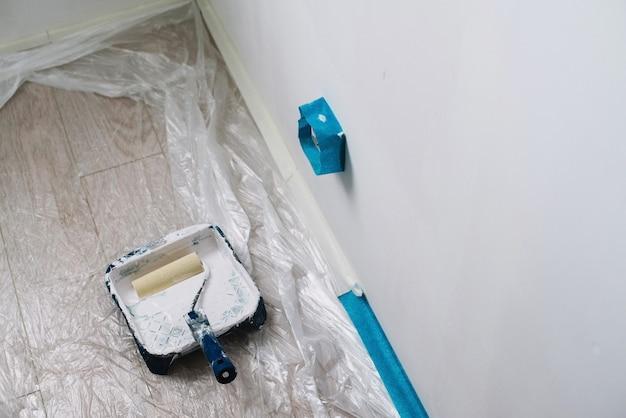 Gros plan sur le pinceau avec douleur blanche, réparation à domicile, peinture murale
