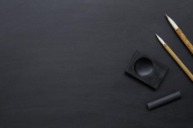 Gros plan pinceau d'écriture traditionnelle du japon sur tableau noir.