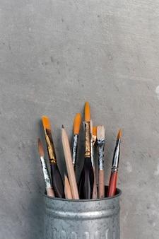 Gros plan de pinceaux dans un vieux pot de métal sale avec du ciment
