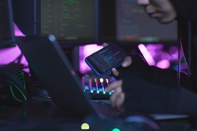 Gros plan d'un pirate informatique méconnaissable portant une cagoule tout en travaillant sur la programmation dans une pièce sombre, copiez l'espace