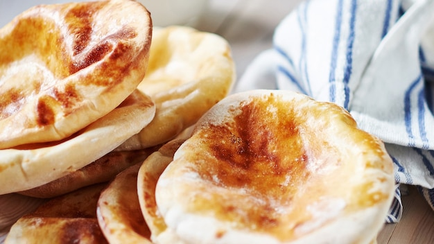 Gros plan de pita pain plat avec du lait à la table blanche wodden. gâteau ohnny frit. cuisine orientale. flapjack d'asie. stile rustique.