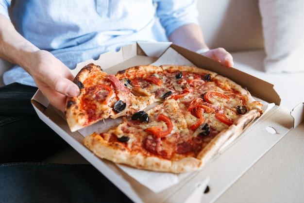 Gros plan d'une pizza en boîte sur les genoux des hommes