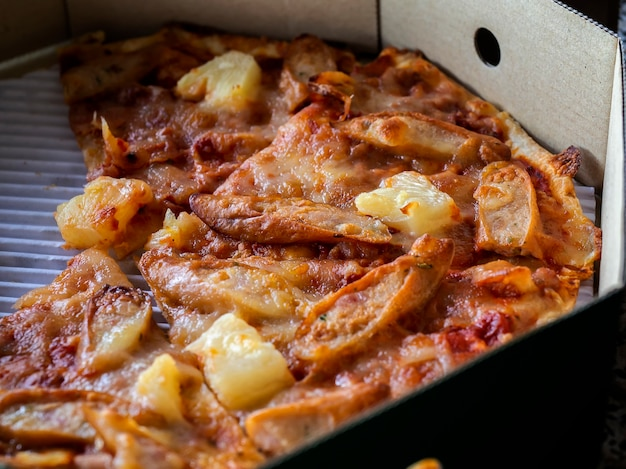 Gros plan d'une pizza fine et croustillante dans une boîte en carton de livraison