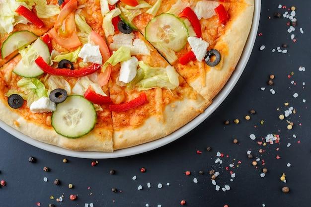 Gros plan de pizza végétarienne avec des légumes sur un fond sombre avec espace de copie