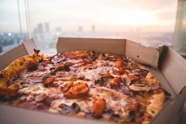 Gros plan de pizza et vue sur la ville.