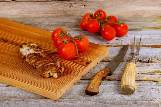 Gros plan sur une planche de bois avec steak de porc grillé à côté de tomates cerises sur table en bois