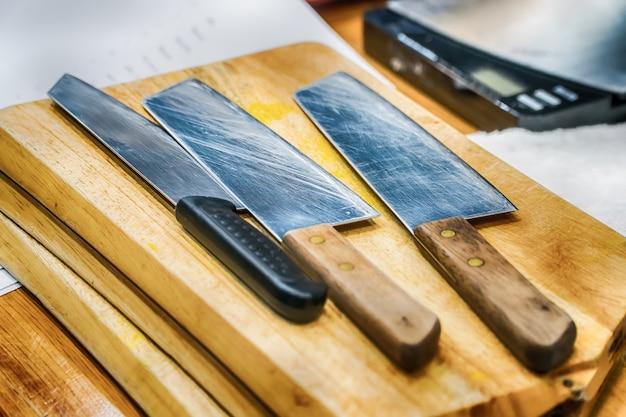 Gros plan d'une planche à découper en bois vieillie, couteau en acier, directement au-dessus