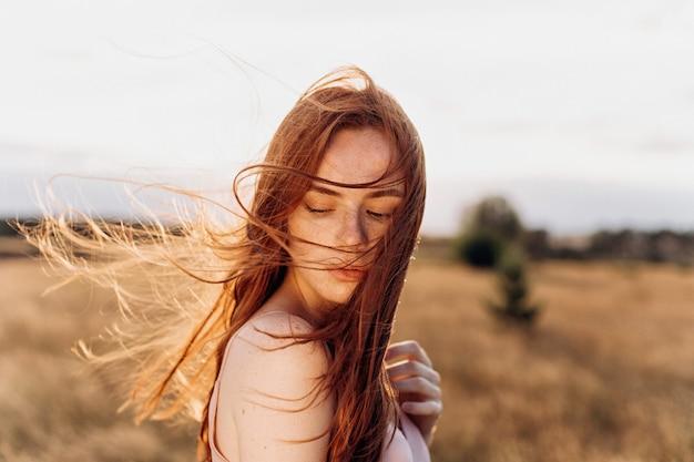 Gros plan en plein air portrait de gingembre jolie fille avec des taches de rousseur sur le coucher de soleil