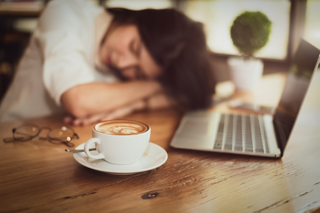 Gros plan de plein de café dans une tasse à café avec une femme d'affaires fatigué de travailler