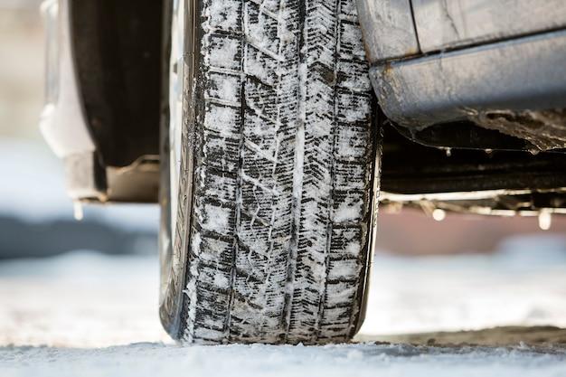 Gros plan d'un pneu de voiture dans la neige profonde.