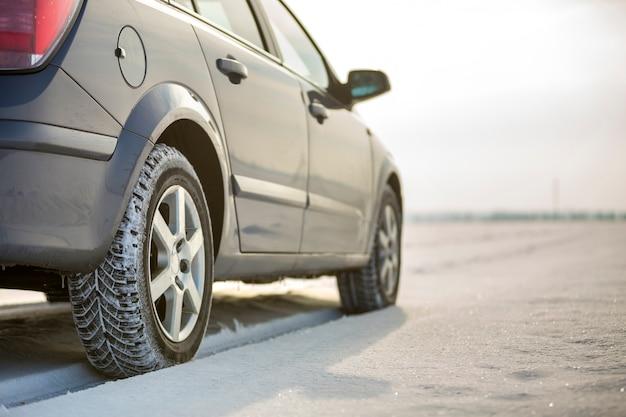 Gros plan d'un pneu de voiture stationné sur une route enneigée le jour de l'hiver. concept de transport et de sécurité.