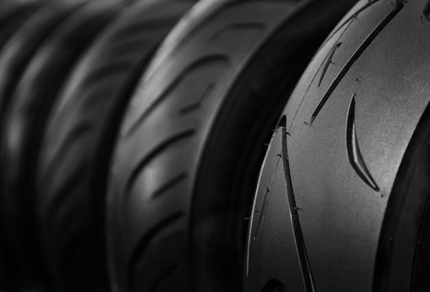 Gros plan des pneus de moto sur rack magasin dans un ton sombre