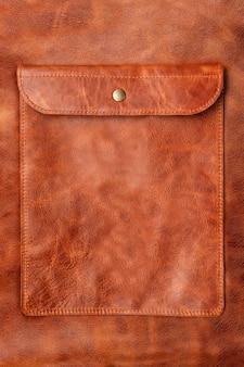 Gros plan sur une poche en cuir marron naturel avec des rayures.