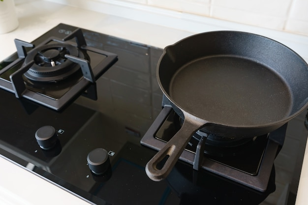 Gros plan de la poêle à frire sur la cuisinière à gaz dans la cuisine moderne moderne haut de gamme.