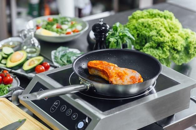 Gros plan sur une poêle à frire et des légumes dans une cuisine professionnelle
