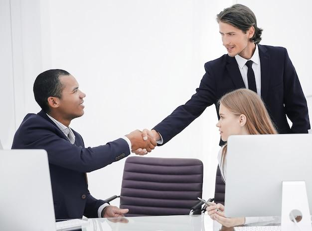 Gros plan .la poignée de main entre collègues sur le lieu de travail