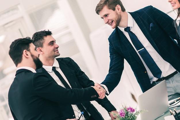 Gros plan d'une poignée de main réussie des partenaires commerciaux après la signature du contrat sur le lieu de travail dans un bureau moderne