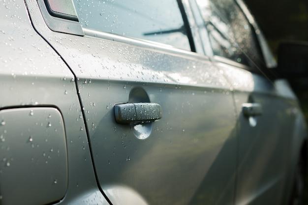 Gros plan de la poignée mouillée de la voiture de porte après avoir chuté dans une scène d'éclairage médiocre. goutte d'eau sur la poignée de porte de la voiture