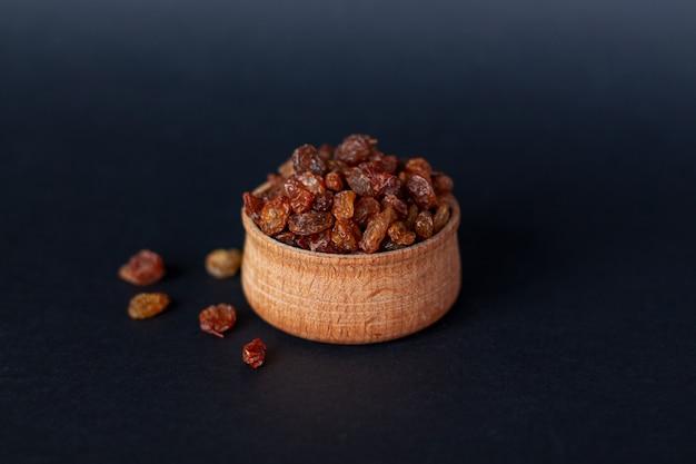 Gros plan, de, poignée, de, raisins secs bruns, sur, bois