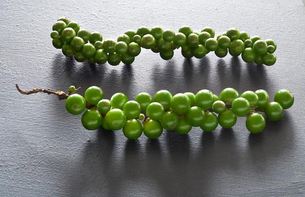 Gros plan sur le poivre vert resh sur gris
