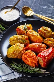 Gros plan de poivrons farcis avec du riz, du bœuf haché et du porc cuit dans une sauce tomate, romarin et thym