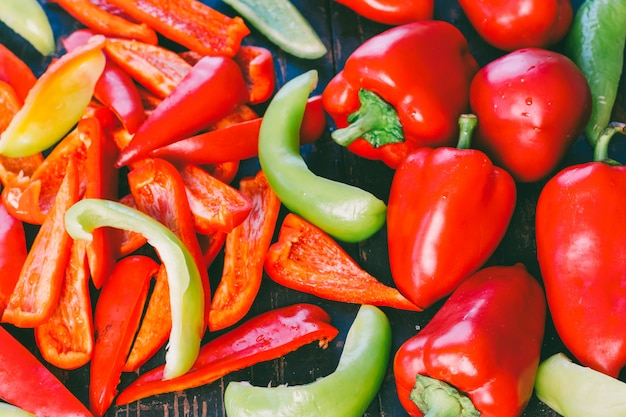 Gros plan de poivrons rouges et verts entiers et tranchés