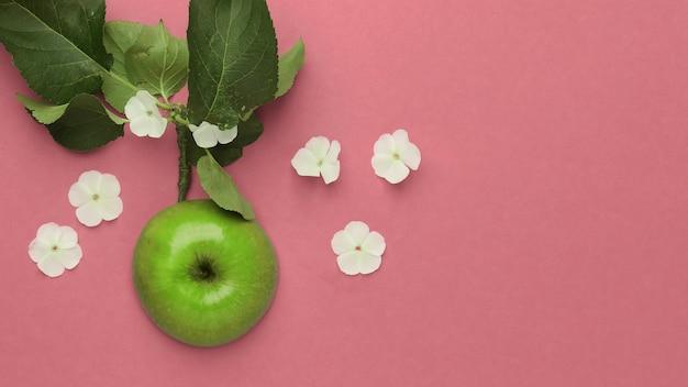Gros plan d'une pomme verte avec des fleurs blanches sur fond rose