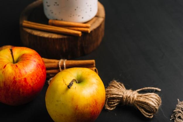 Gros plan et pommes près de la cannelle et de la tasse