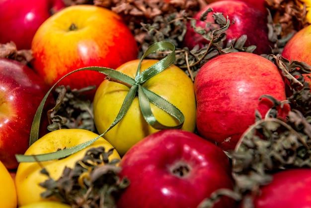 Gros plan de pommes rouges et savoureuses sur fond de mousse verte, décoration cadeau avec ruban vert