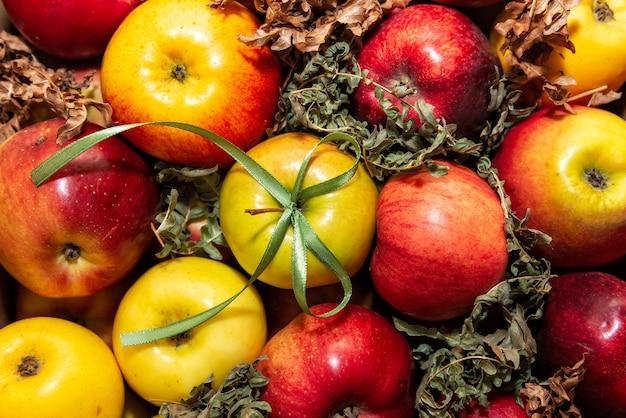 Gros plan de pommes savoureuses rouges sur fond de mousse verte, décoration cadeau avec ruban vert