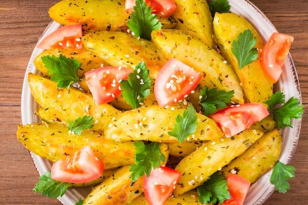 Gros plan de pommes de terre au four dans une pelure avec des tomates, des herbes, des épices et du sésame dans une assiette, vue de dessus