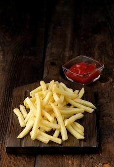 Gros plan de pommes de terre frites faites maison avec sauce sur table en bois.