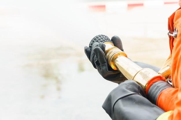 Gros plan de pompier main pulvériser de l'eau du tuyau. entraînement au feu avec espace de copie
