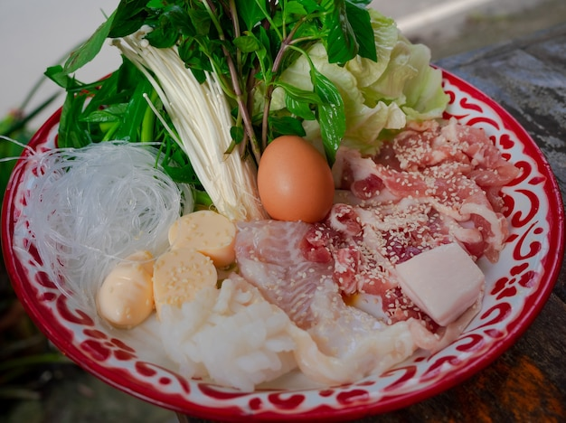 Gros plan de porc mariné frais, poisson, œuf, tofu, vermicelles et légumes sur assiette, ensemble d'ingrédients pour barbecue de style thaïlandais ou moo krata