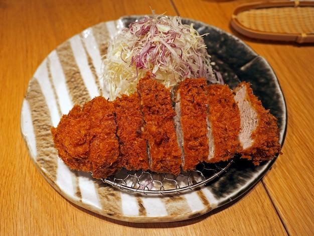Gros plan de porc tonkatsu (porc frit japonais avec chapelure croustillante) sur table en bois