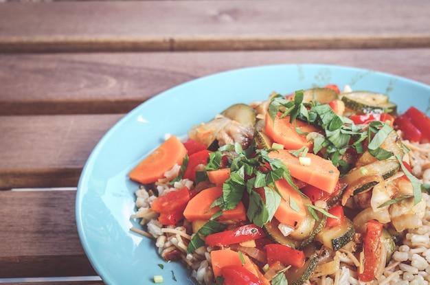 Gros plan de porridge avec de la viande de poulet et des légumes frais coupés sur une plaque bleue