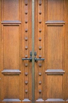 Gros plan de la porte en bois ancienne avec poignées en fer orné