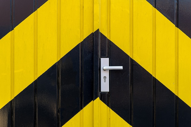 Gros plan d'une porte avec des rayures noires et jaunes
